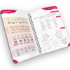 Open spiral-bound planner with reference guides.