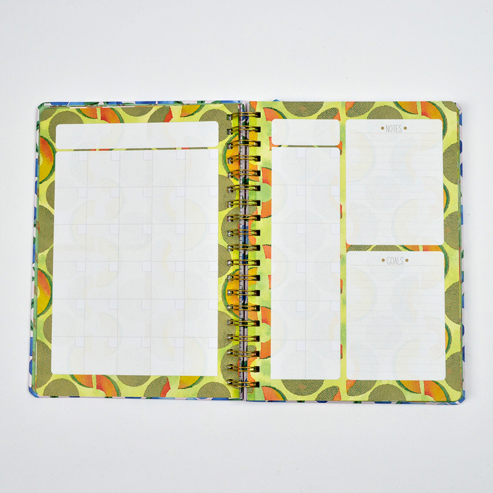 Open spiral-bound planner with month view.