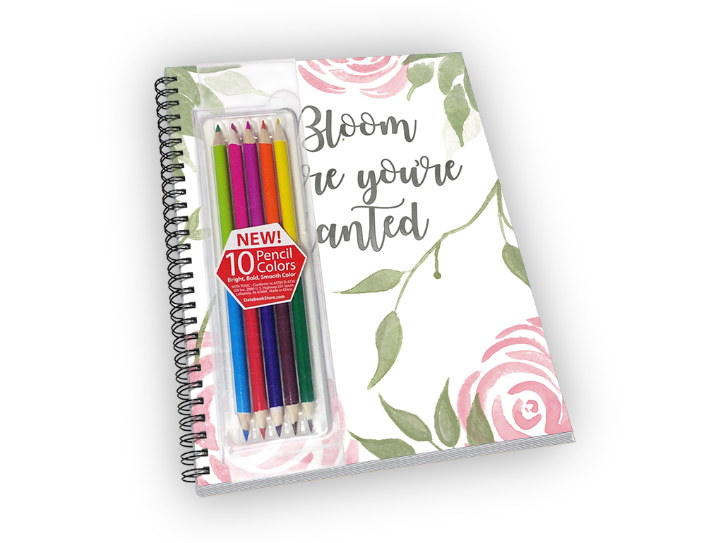 Mid-sized spiral-bound notebook with a rose bloom cover and colored pencils.
