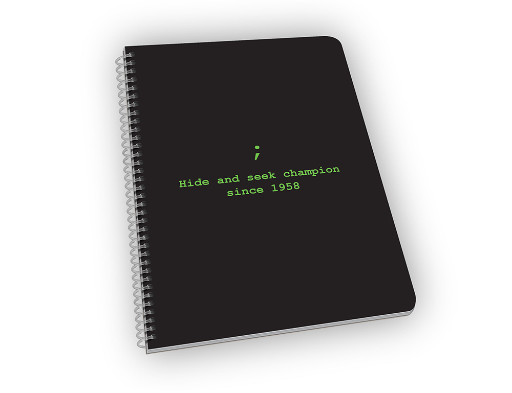 Spiral-bound notebook with coding joke on cover.