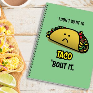 Scene of spiral-bound notebook with a taco carton on the cover.